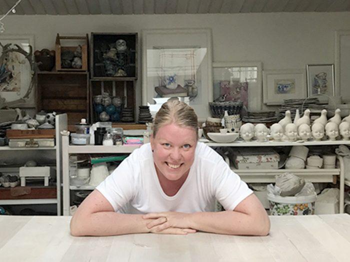 Ägaren, Pernilla lutar sig över ett bord i sin atelje. Bakom henne kan man se massor av hennes keramik.
