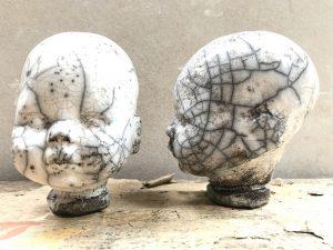 två stycken keramikhuvuden med rakubränning. De är vita med brunt insalg