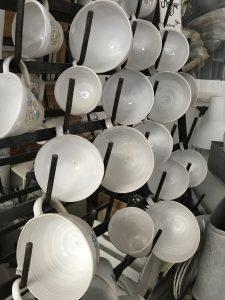 stora koppar hänger i ett koppställ i ateljen.