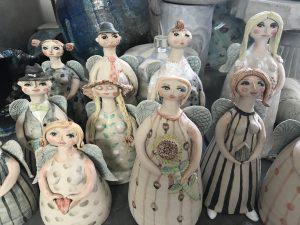 Nio stående skulpturer i form av små minimänniksor i olika mönstrade klänningar, långa flätor och hattar. Alla har vingar.