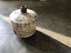 en liten vas med liten öppning i rakumönster. Vasen är vit med bruna inslag