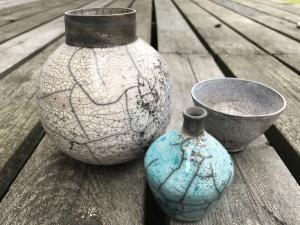 två olika keramikvaser i olika storlek står jämte en liten keramikskål
