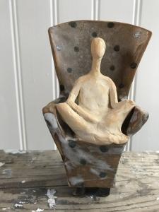 en skulptur i form av en beige människa som sitter i en brun fotölj med svara prickar på.