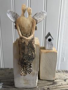 en sittande skulptur i form av två änglar som sitter jämte varandra med änglavingar på ryggen. Jämte änglarna finns en skulptur i form av en liten fågelholk