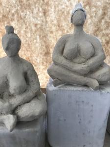 två skulpturer i form av nakna kvinnor som sitter ned i skräddarställning.