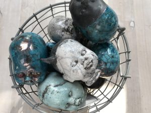 Många huvudskulpturer med raku mönster ligger i en korg av metall