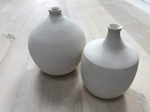 två stående vaser, båda är vita och hade en rund form.