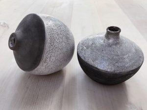 två stycken vaser står på ett bord. De är tvåfärgade. Halva vasen är svart och halva vasen har ett vitt rakumönster