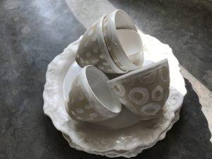 flera olika keramikskålar ligger på glansiga,romantiska keramik fat