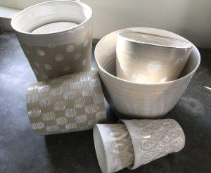 Vita och prickiga keramikskålar i olika storlekar ligger och står upp på en stenbänk