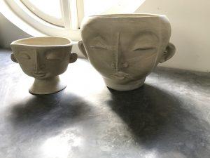 två stycken vaser i en form som ett ansikte med öron, ögon näsa och mun
