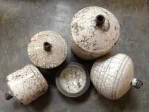 fyra stycken små, olika vaser i rakumönster. De är vita med brunt inslag. Det finns även ett litet fat i samma färg på bilden.