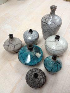 Sju olika vaser med rakumönstring på sig. Två är turkosa och resterande fem är av olika grå nyanser.