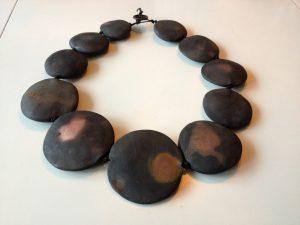 ett svart halsband med olika runda cirklar på ett snöre