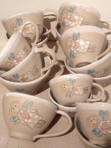 beige keramikmuggar med änglamotiv på.