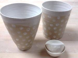 Två stycken olikformade kaffe muggar i beige färg med vita prickar på. Muggarna är utan öra. Bilden visar även två små vita skålar