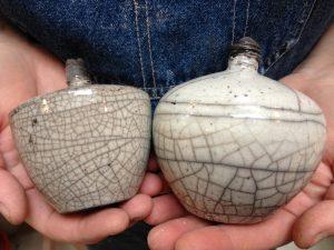 två händer håller varsin vas i mönster av raku. Vaserna är vita och bruna